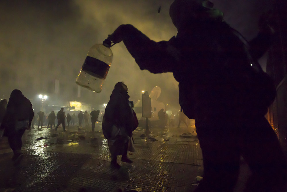 A small group of protesters throw trash against the police after police forces started using water cannons to disperse the crowd that had gathered near the Senate to hear the final vote on a bill that would de-criminalize and legalize abortion in Buenos Aires, Argentina, on Aug. 8th, 2018.