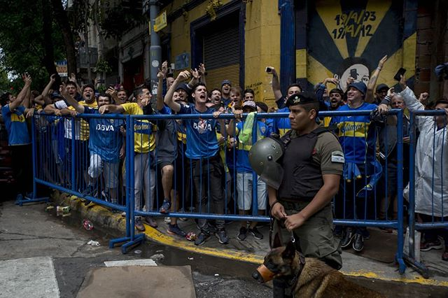 Fans cheer as they wait before police open the gates to the first security ring, hours before the first leg of the final. Police presence was abundant in the neighborhood, where you couldn't walk more than a single block without seeing a group of 10-15 city police, federal police, or gendarmes.  #onassignment for @espn #boca #buenosaires #argentina