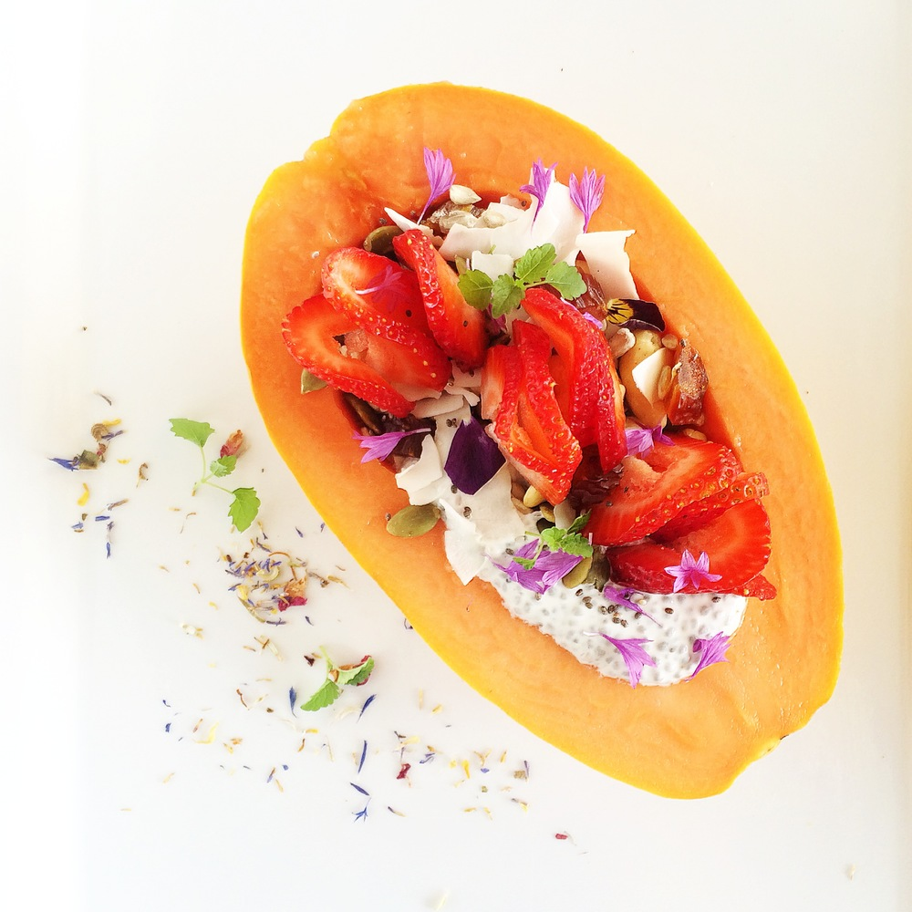Papaya edibowl with cornflowers and strawberry buds
