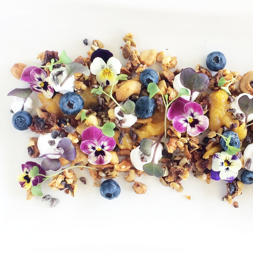 Edible viola garden with granola stones, coconut yoghurt, mango puree, and berries