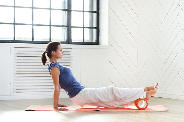 woman rolling out muscles on the floor.jpg