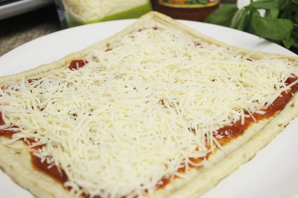 Sprinkle the shredded mozzarella and parmesan evenly over the pizza sauce.