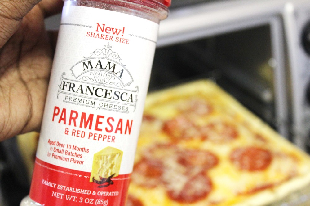 Now you're ready to garnish your pizza with the parmesan, red pepper, and fresh basil. Add a pop of green to make it Instagram-ready!