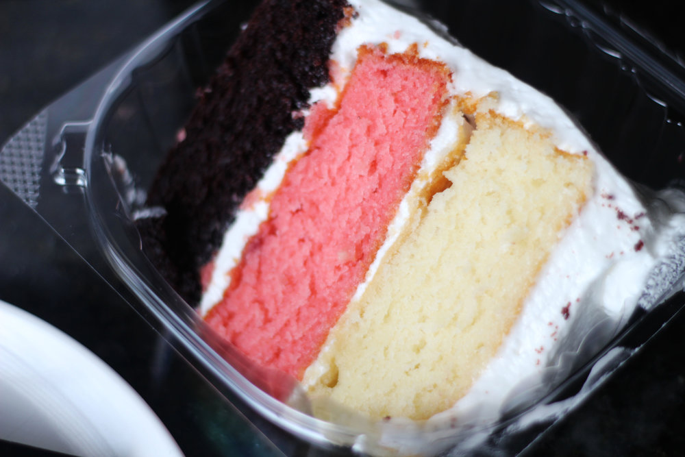 Slice of Neopolitan cake from Cake Bar at Trinity Groves (chocolate, strawberry, and vanilla layers).