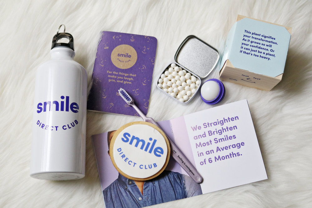 SmileDirectClub swag bag with a water canteen, notebook, a soft bristle toothbrush, tin of mints, lip balm, an Italian oregano plant to grow, smile cookie, and an booklet full of must-know information about the process.