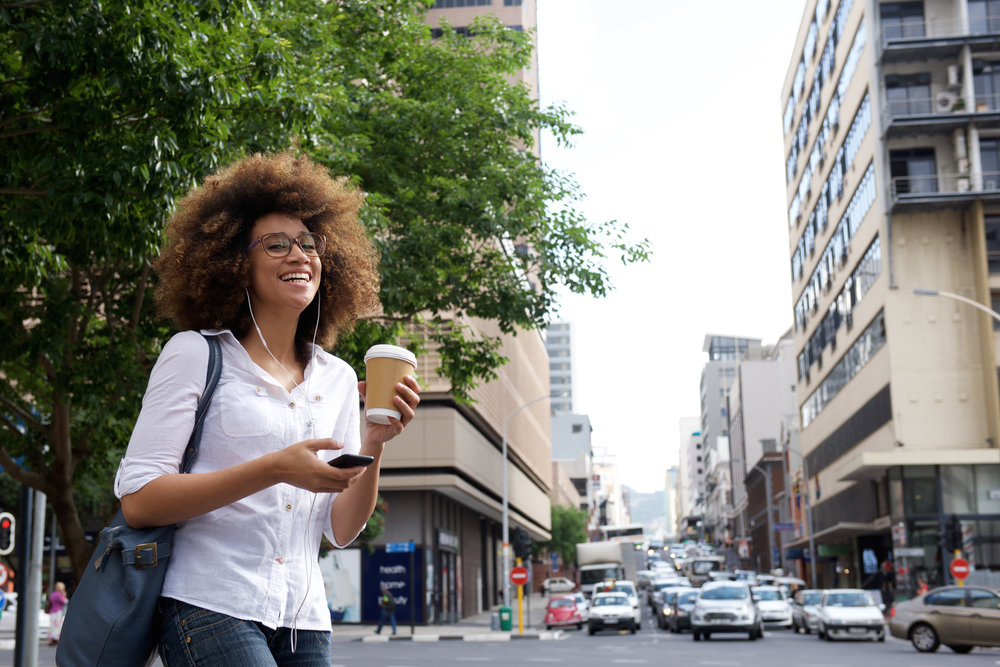 cheerful-woman-walking-in-the-city-with-cell-PWRTA5G.jpg