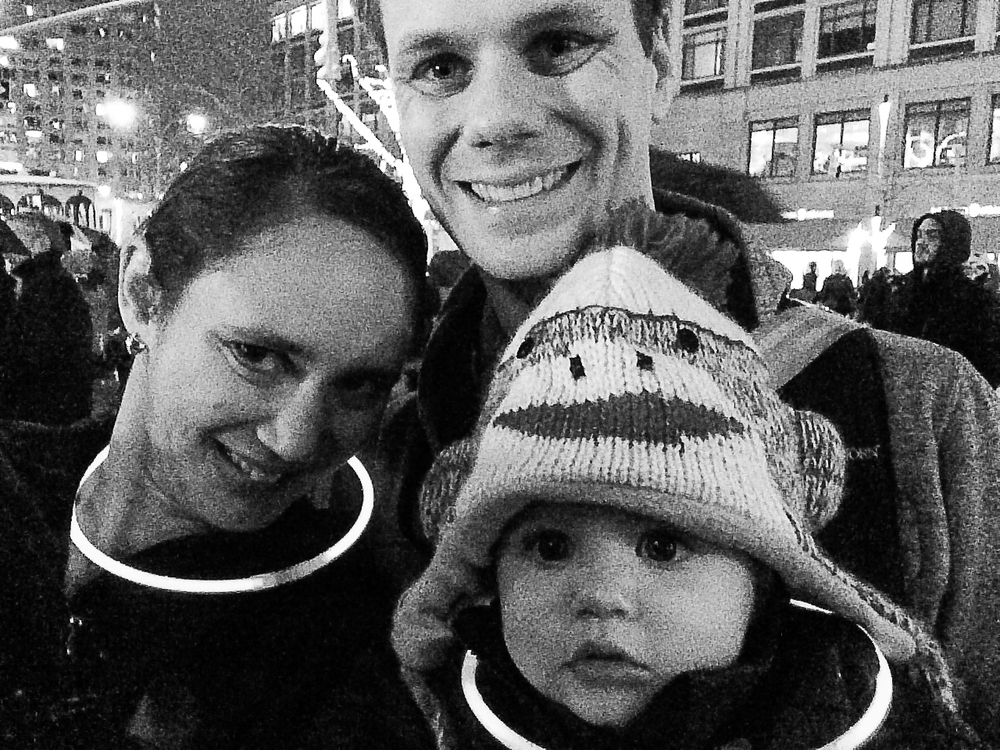 Family Winter's Eve grainy selfie as we waited in the rain for the tree lighting to start. Love that they gave out free glow sticks for everyone to wear.