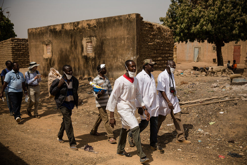 Ike walks behind a team of entomologists in the village of Bana, Burkina Faso who are part of an international project to use genetically engineered mosquitos to eliminate malaria. Photo by Sophie Garcia.