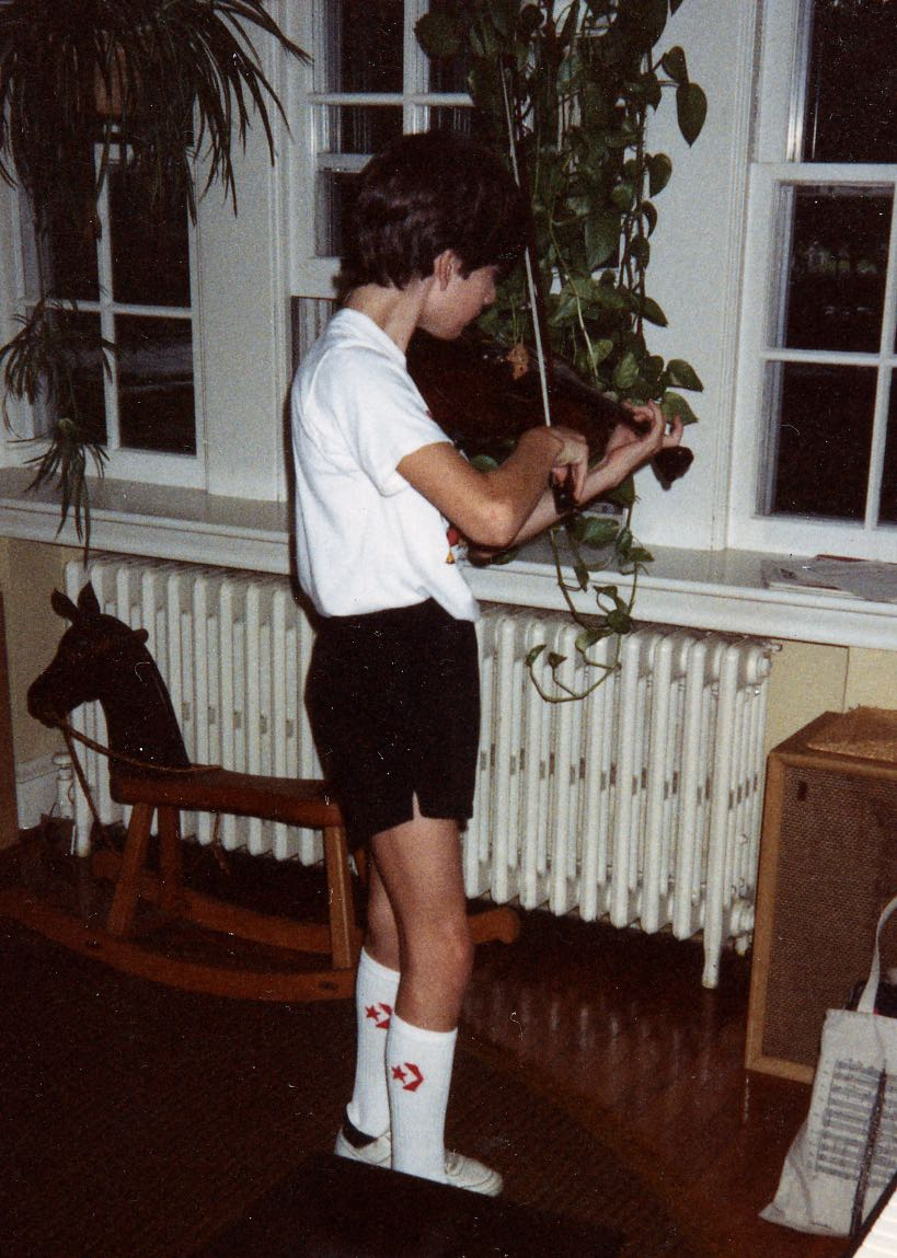 An awkward instrument made more awkward by how it's held: a thirteen year old contorts his body to play the violin.