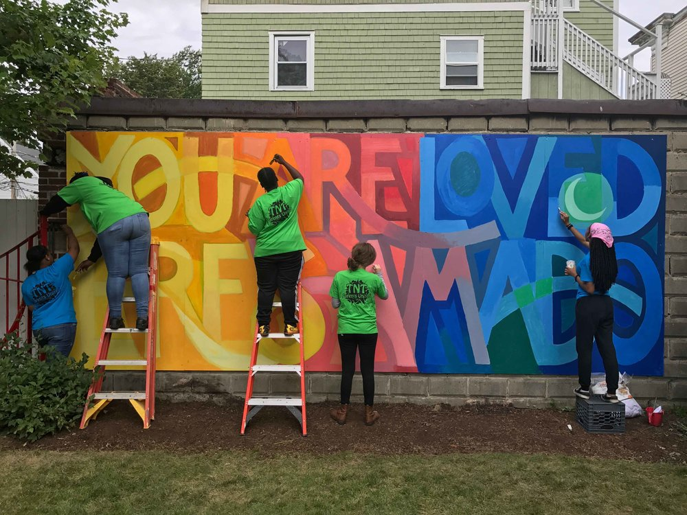 A teen work crew from Boston Project Ministries paints a mural at Elmhurst Park in Dorchester, MA
