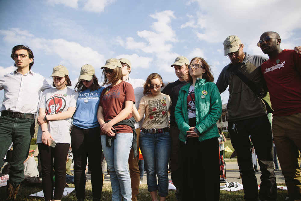 Alex Clemetson, a student at the Methodist Theological School in Ohio (FAR RIGHT), joins the OSU student fasters with whom MTSO students fasted in solidarity this week, after leading a prayer for farmworkers and allies present at the vigil