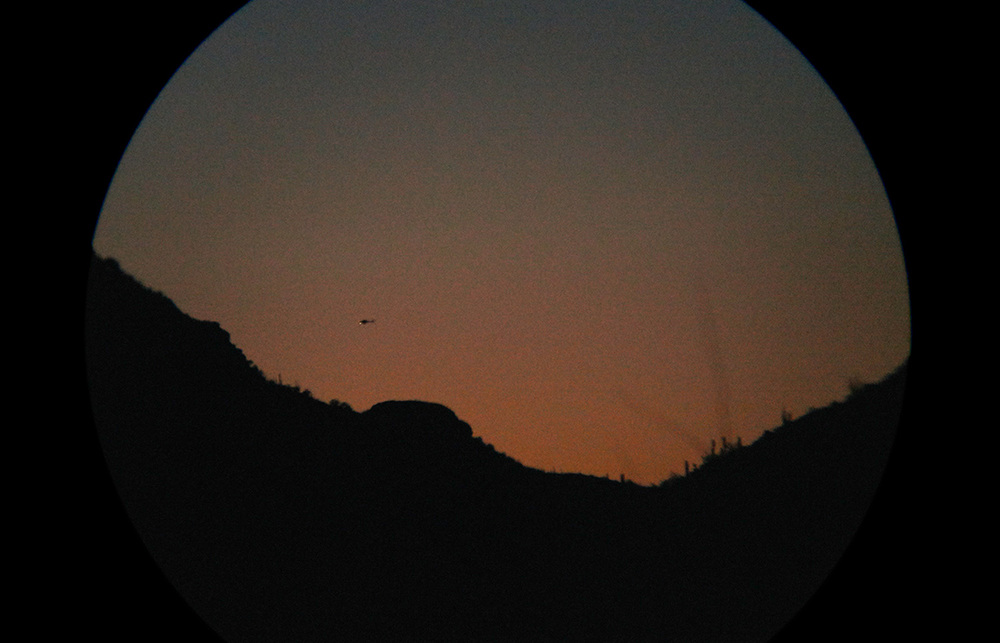 Hovering over smugglers: Border Patrol helicopter through binoculars at sunset, 2013