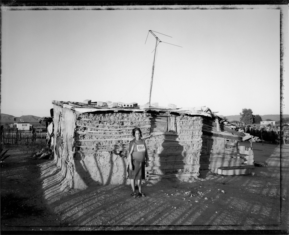Woman with house made of adobe and saguaro ribs, US-Mexico border, 1993