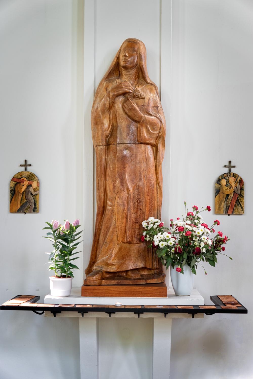Den hellige Therese af Lisieux   Skt. Thérèse ønskede højt at følge sin søster, Pauline som var indtrådt som nonne i Karmeliter-ordenen, men hun var som 14 årig for ung og blev afvist. Et kendetegn ved Skt. Thérèse var, til trods for at hun er kendt som Den lille Blomst, hendes beslutsomhed og stædighed, så efter afvisningen gik hun til den lokale biskop for at få hans tilladelse. Igen uden held. Hendes far og ældre søster, Celine indså at de ikke kunne tale Skt. Thérèse fra sin ide, hvorfor de alle tre drog på pilgrimsrejse til Rom for derigennem at få hende fra ideen. Her tog de gruelig fejl! Under en audiens med pave XXX brød hun alle protokoller og påbud, og bønfaldt paven om tilladelse til at blive optaget i Karmeliterordenen som 14 årig. Hun blev båret ud af to vagter fra Schweizergarden. Skt. Thérèse blev imidlertid optaget i ordenen kort tid efter, da pavens Generalvikar var blevet overbevist om hendes kald.  Skt. Thérèse forbliver igennem hele sit liv novice, selv efter at storesøsteren Pauline bliver udpeget til priorinde. Det var en tid med intern uro i klosteret, hvor flere var bange for at de tre søstre ville blive for dominerende. For at berolige gemytterne bad Pauline hende om at forblive novice, og dermed underlagt de øvrige nonner.  Skt. Thérèse levede og arbejdede bag klostrets mure i reflektion over, hvordan hun bedst kunne tjene Gud, da hun som novice og i karmeliterordenen ikke ville kunne udføre store, synlige helgensgerninger. Men i 1896 begyndte hun at hoste blod op. Hun nævnte ikke dette for nogen, men hendes sygdom blev åbenlys for alle et år senere, hvor hun var for syg til at kunne arbejde. Skt. Thérèse var fortvivlet over at skulle dø ung, og ikke efterlade sig et aftryk efter sin død, hvorfor Pauline bad hende om at nedfælde sine erindrer til eftertiden.  Skt. Thérèse døde af tuberkulose under store lidelser den 30. september 1897, kun 24 år gammel. Hun beskriver sine smerter som værende så stærke, at hvis hun ikke havde haft sin tro, v