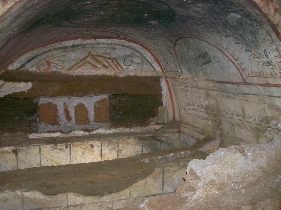 View inside of an arched burial niche or arcosolim inside of the Villa Torlonia catacombs. The walls, vault, and even the insides of the burial troughs were originally plastered and painted, but were subsequently damaged by additional burials in the back wall and above the original tomb covers. Photo: International Catacomb Society