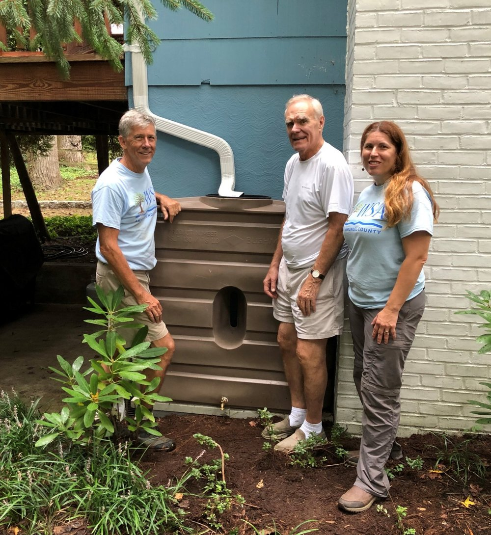 Steward Candidate Thomas Marston (left) and Katie Matta (right) installed a rainbarrel on Marc Wirig's home in Hillsmere.