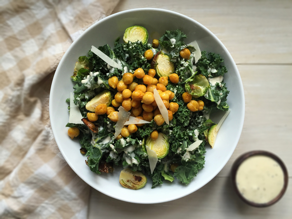 Surprise your guests with this delicious and deeply nourishing spin on Caesar Salad! Kale is easier to digest if you do some of the breaking down ahead of time; aka massage those greens! Just a glug of dressing or olive oil will do, with a pinch of sea salt, then squeeze and massage your stress away, until the kale is soft and palatable. Add some roasted Brussels sprouts for some warm, soft goodness, and drizzle with the creamy cashew dressing, which adds necessary, brain boosting fats.