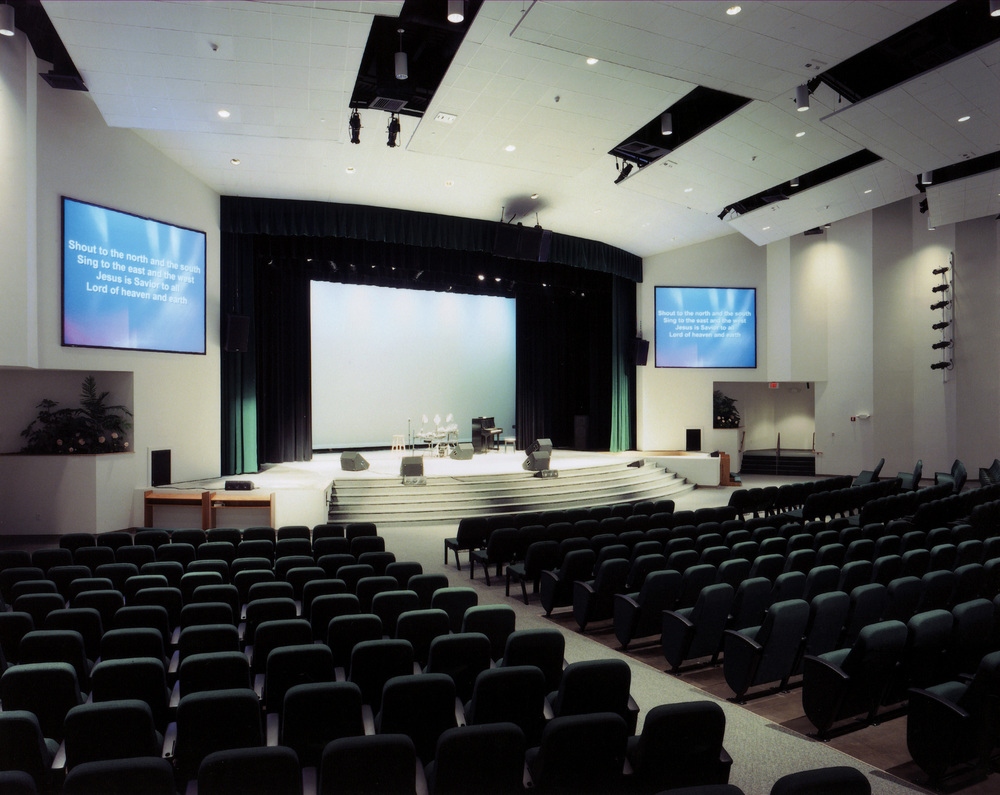 This expandable worship center designed for walnut hill community church in bethel, CT. has the unique feature of a 3-part floor. the front most section is flat to accommodate round tables for dinner-theater productions, while the central band os seats is on a sloped floor, and the expansion section (Removable back wall) is amphitheater seating. Total capacity 1,400 seats.