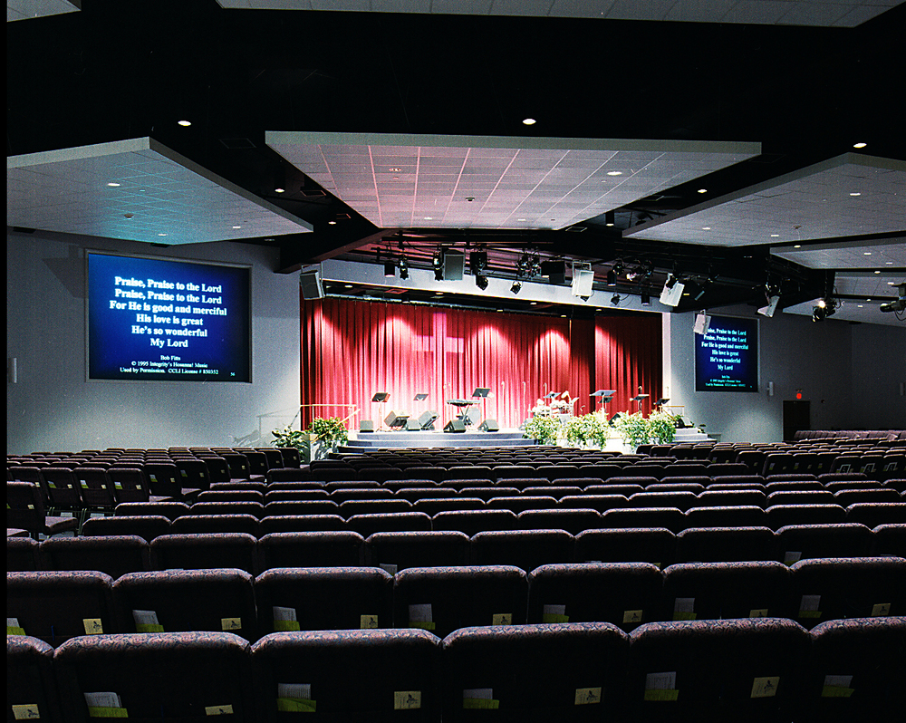 Transforming a grocery store into a 1,000 seat auditorium for grace fellowship was accomplished in 6 months, including the removal of several columns that obstructed sight lines. a higher stage was utilized to compensate for the flat floor.