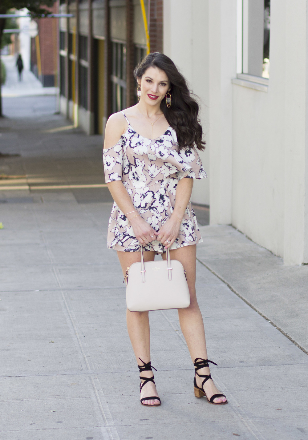 Summer date night outfit, JOA floral print cold shoulder romper, Steve Madden Rizzaa sandals, Kate Spade Cedar Street Maise, J.Crew denim jacket with DIY embellishment, statement earrings, and NARS red lipstick.