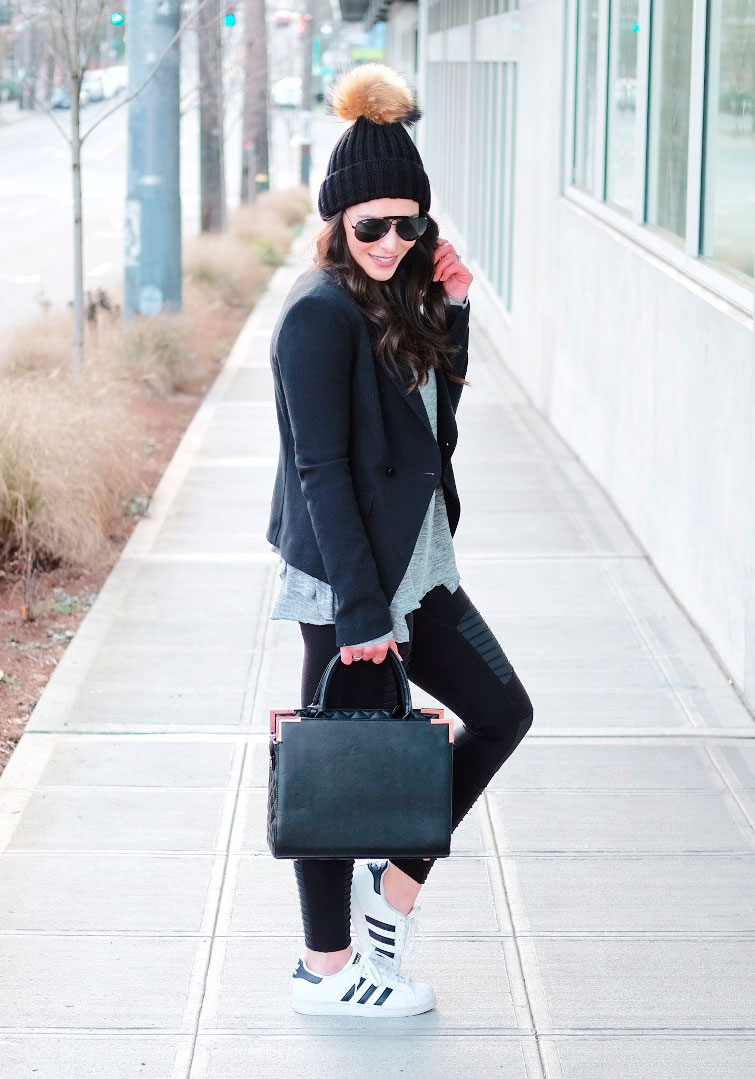 Athleisure outfit.  Alo Yoga moto leggings, Adidas Superstars, Ruffle hem tee, jersey blazer, pom pom beanie, and black Ray-Ban aviators.