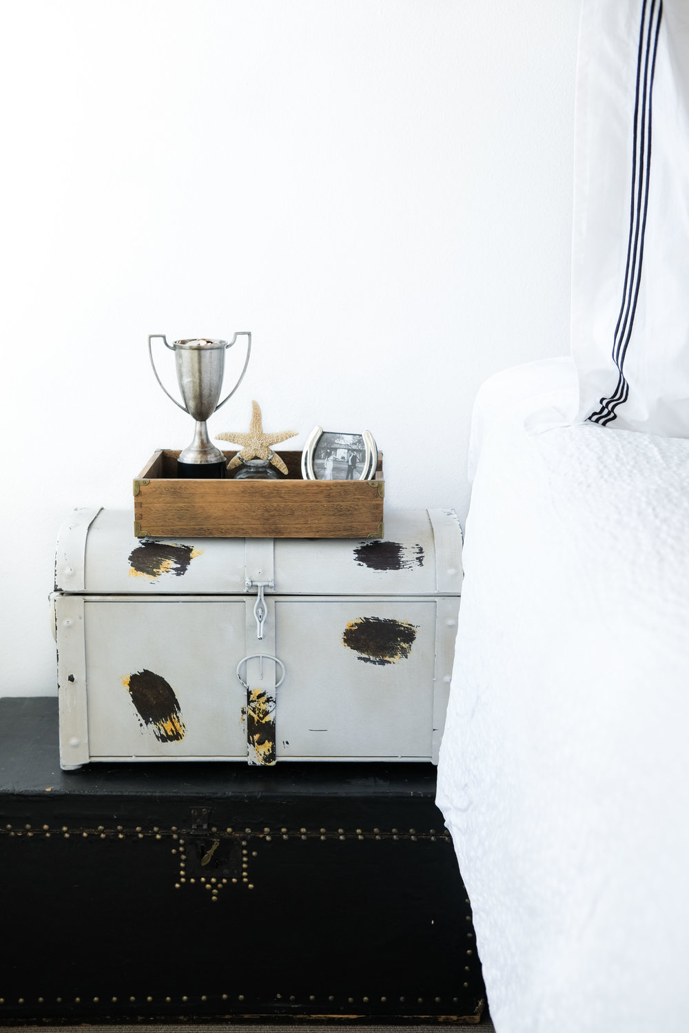 Storage hacks for small bedrooms.  DIY vintage trunk bedside table nightstand.  Modern loft decor.  All white master bedroom.  Pottery Barn grand embroidered sham.