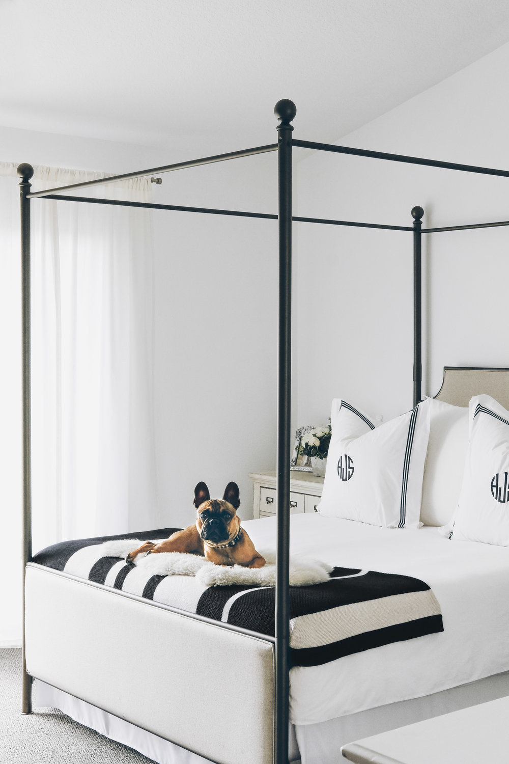 Black and White Vintage Industrial Bedroom.  Joss & Main Marianne Upholstered Canopy Bed, Olympus Nightstands, Pottery Barn Grand Embroidered Euro Shams and striped blanket.