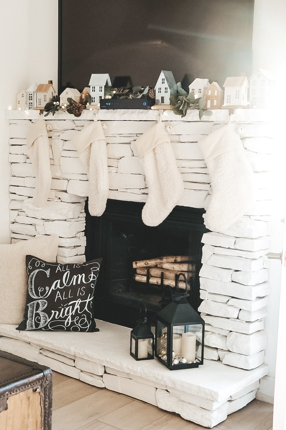 White Christmas decor.  Galvanized and wooden houses on the mantle for Christmas.  White fur stockings.