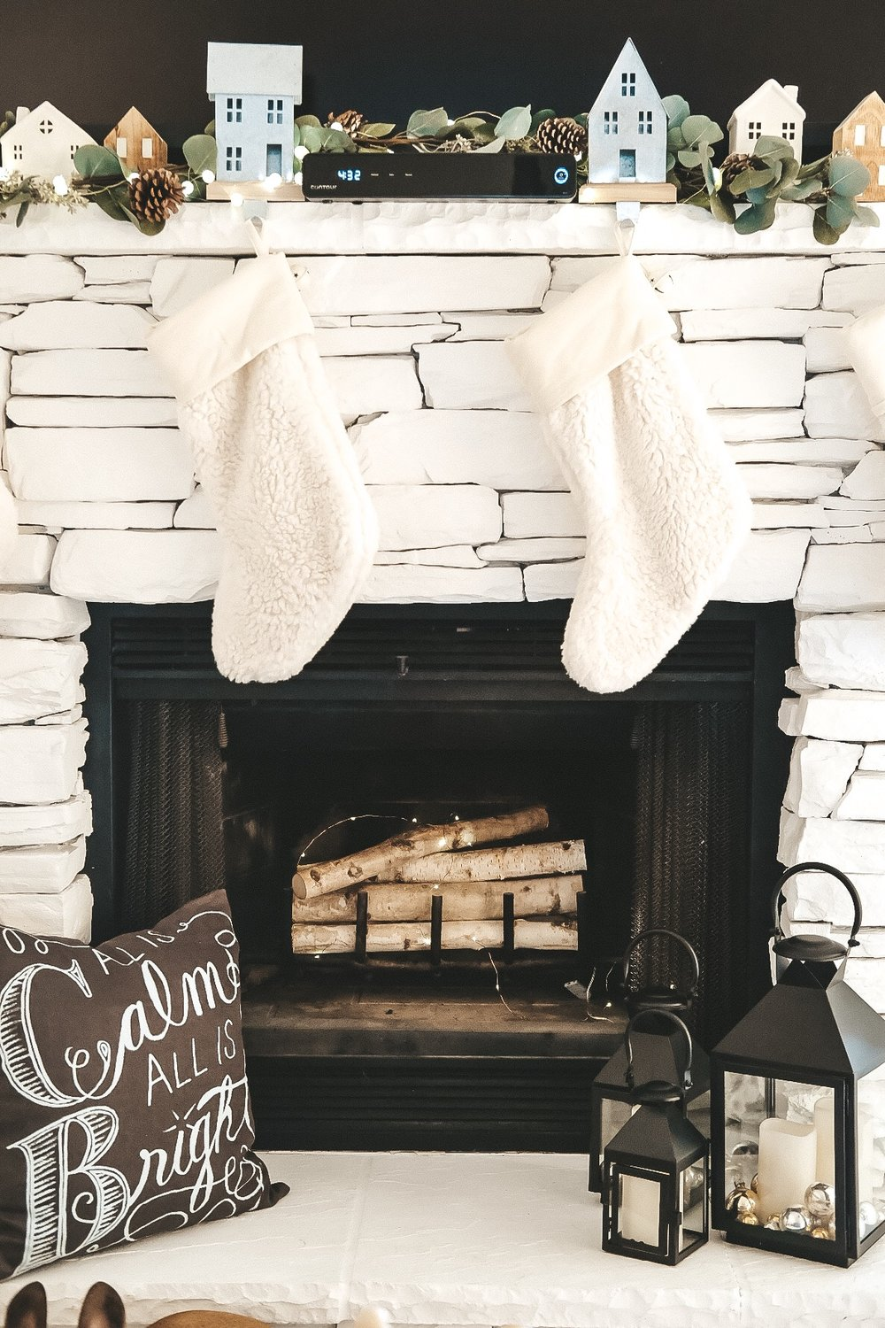 White Christmas decor.  Mantle with faux fur stockings and galvanized houses.