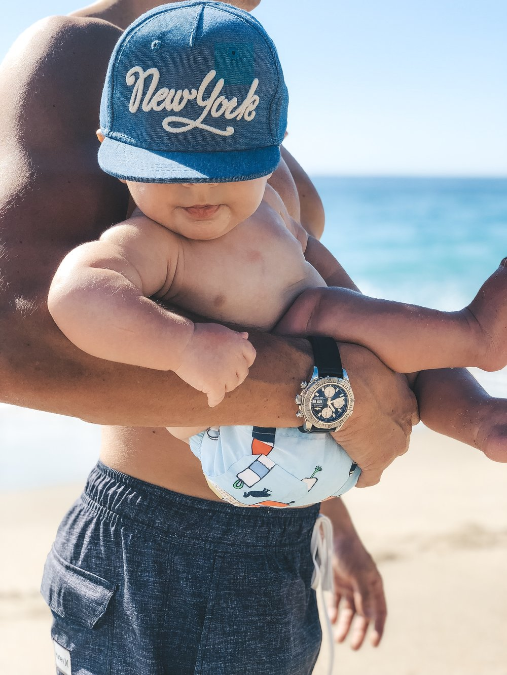 How to take better photos of your baby.  Best camera for photographing children and babies. Daddy and baby at the beach.  The Beaufort Bonnet Company swim shorts.