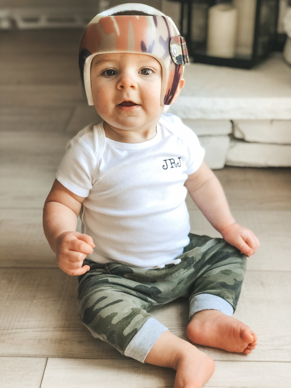 Jett Jones 10 months old.  Monogrammed onesies for babies.  Camo joggers from baby Gap.  Camo starband helmet from Hangar clinic.