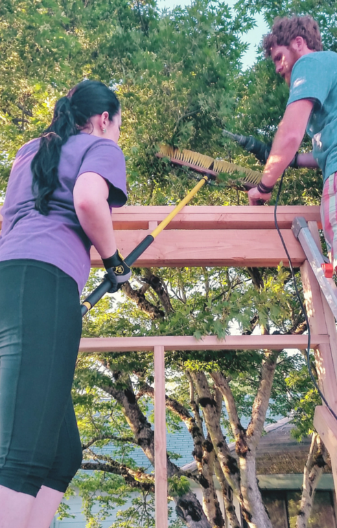 On a ladder, holding a 2x4 in place with one hand, and using a broom to shove a branch out of Nick's face with the other....don't turn me in to OSHA...