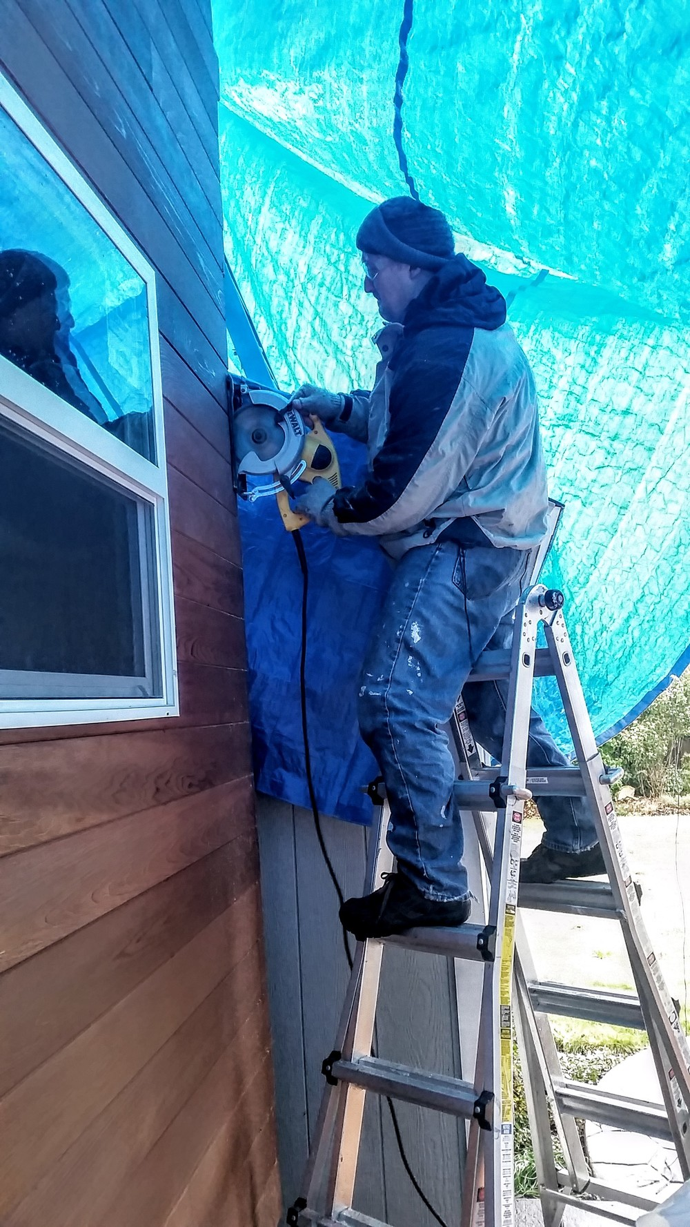 Dad trimming off the extra bits to fit the corner pieces on over the siding