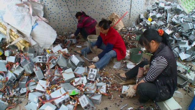 Women in Guiyu, China pick out precious metals from dumped e-waste