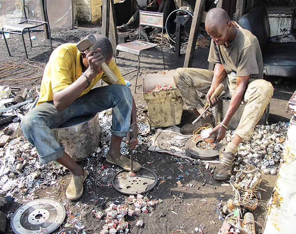 Two people harvest metal scraps from e-waste in Ghana