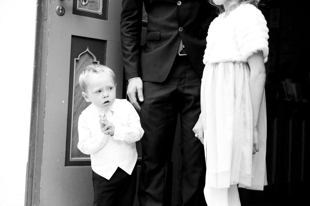 Spent og forventningsfull gutt som venter på å se Mamma i brudekjole