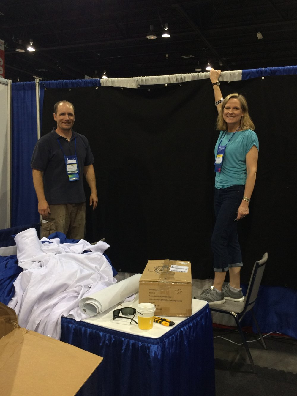 Kristin Miller Burrell and Greg Hughes setting up Continuum Games booth at ASTRA