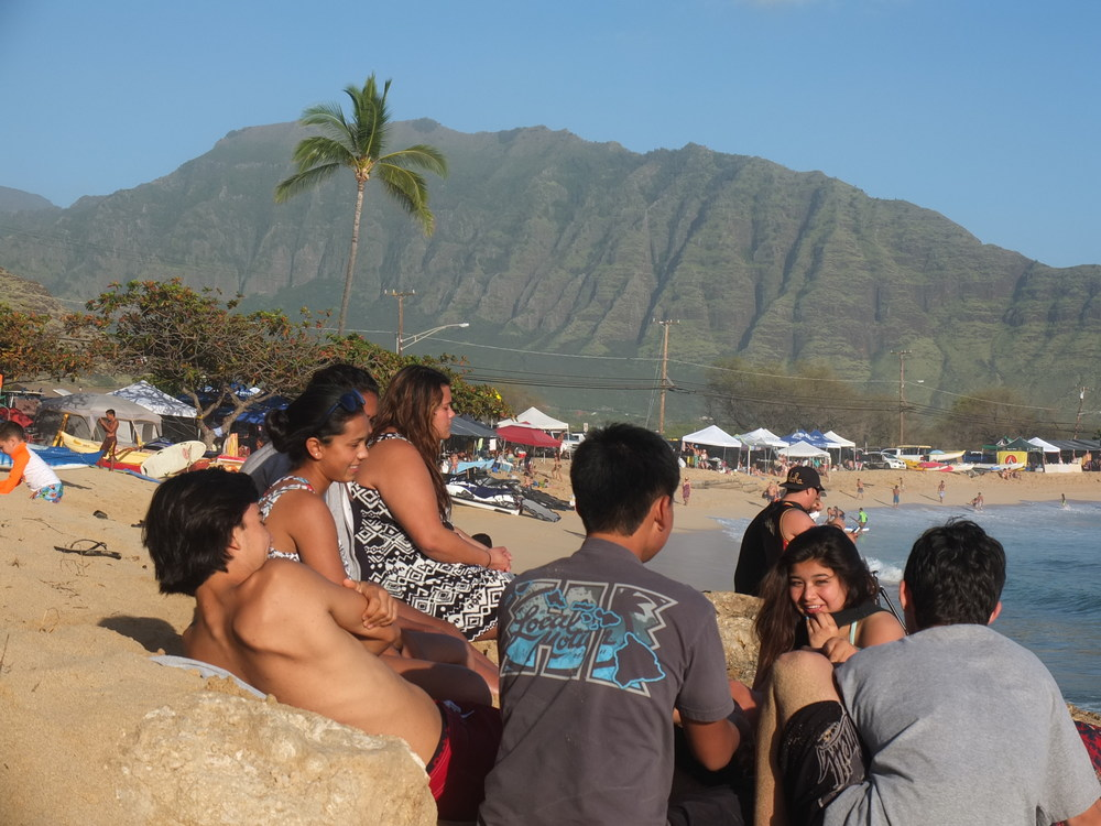 Na Kama Kai Youth exchange some social time during the Buffalo Big Board Classic in Makaha. This legendary contest, gathering, is the oldest surf contest in the world and brings ultimate prestige in water sports. Today the waves were over 20ft so youth talked story and watched from the beach.