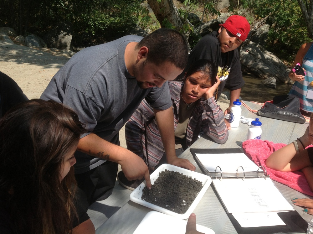 "JUst Schmidtt (La Jolla Reservation) is an InterTribal Youth Alum and went to intern for our NSF ""Sharing the Land"" Program, before working for his Tribes EPA. Today, Intertribal High School youth learn from Justin as he monitors the health of the tribes soil and non-source water pollution."