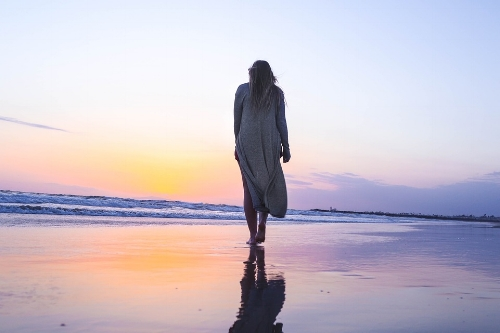 woman walking alone on beach.jpg