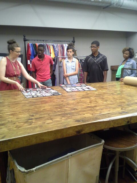 Teens from Team Village Fashion learning about design from Oobe, a local clothing manufacturer.