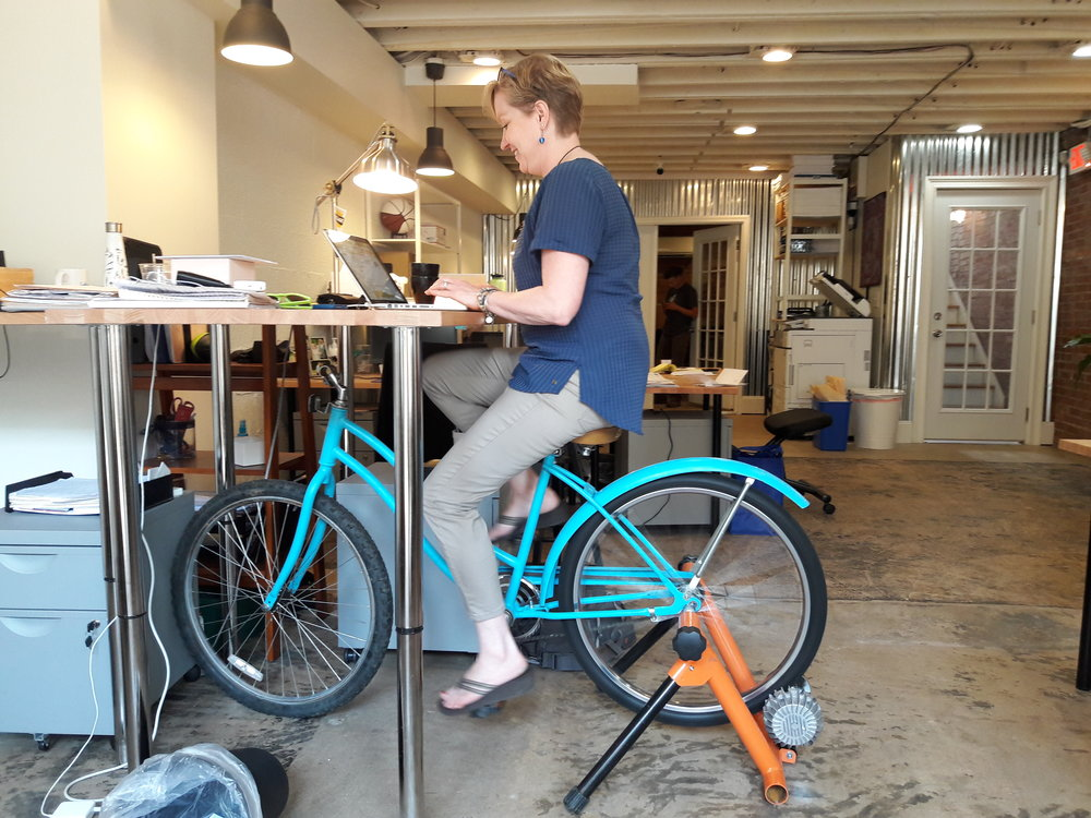 Textile Hall member, Sherry, taking a spin on the new bicycle desk.