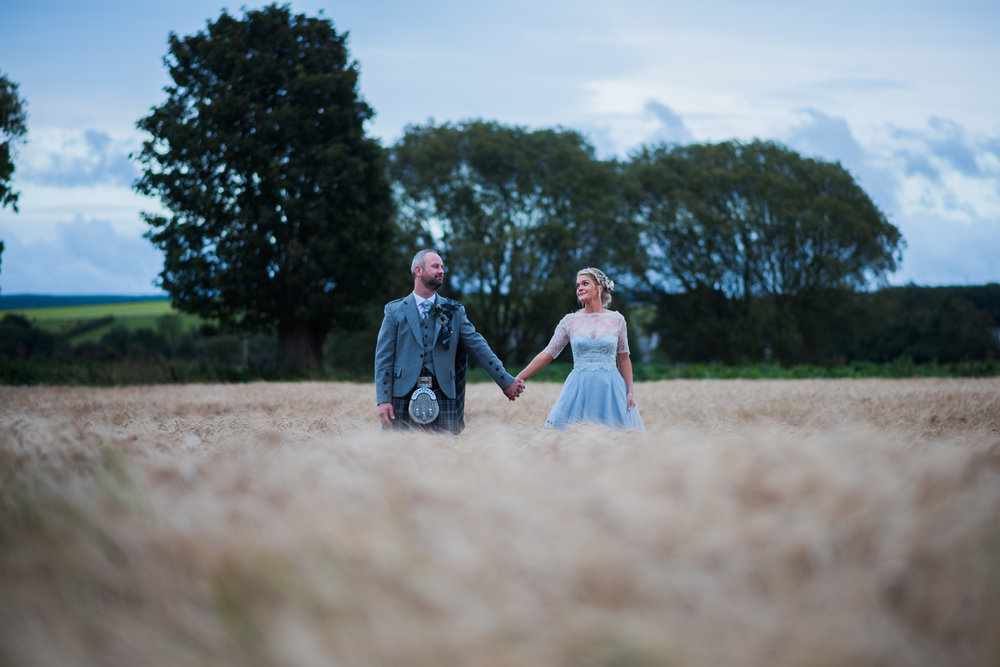 Bride and Groom standing in field at Dalduff Farm