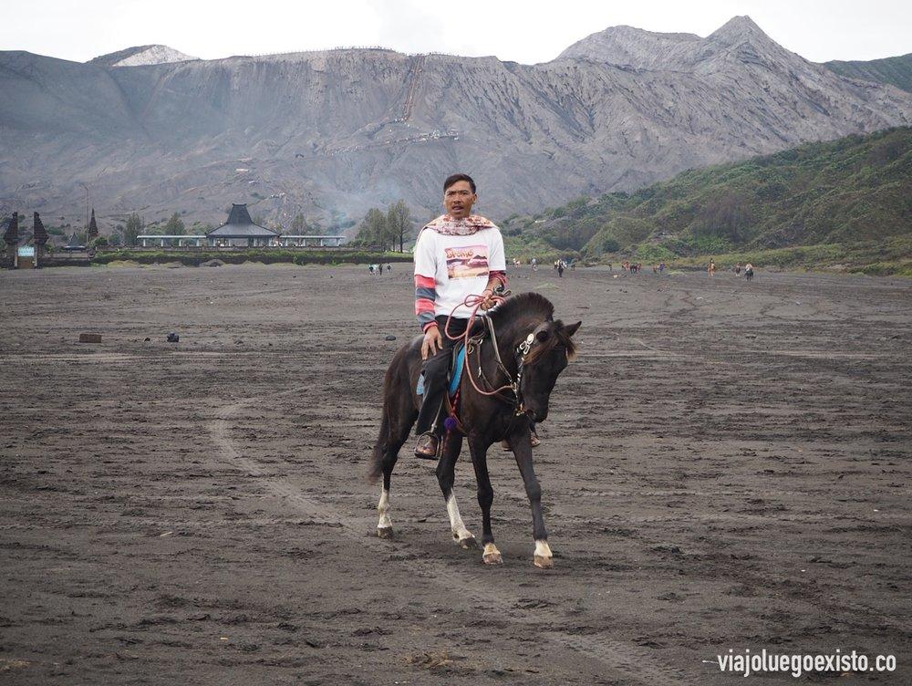Local en caballo, los usan para llevar a turistas hasta el pie del cráter. De fondo se ve el templo Pura Luhur Poten