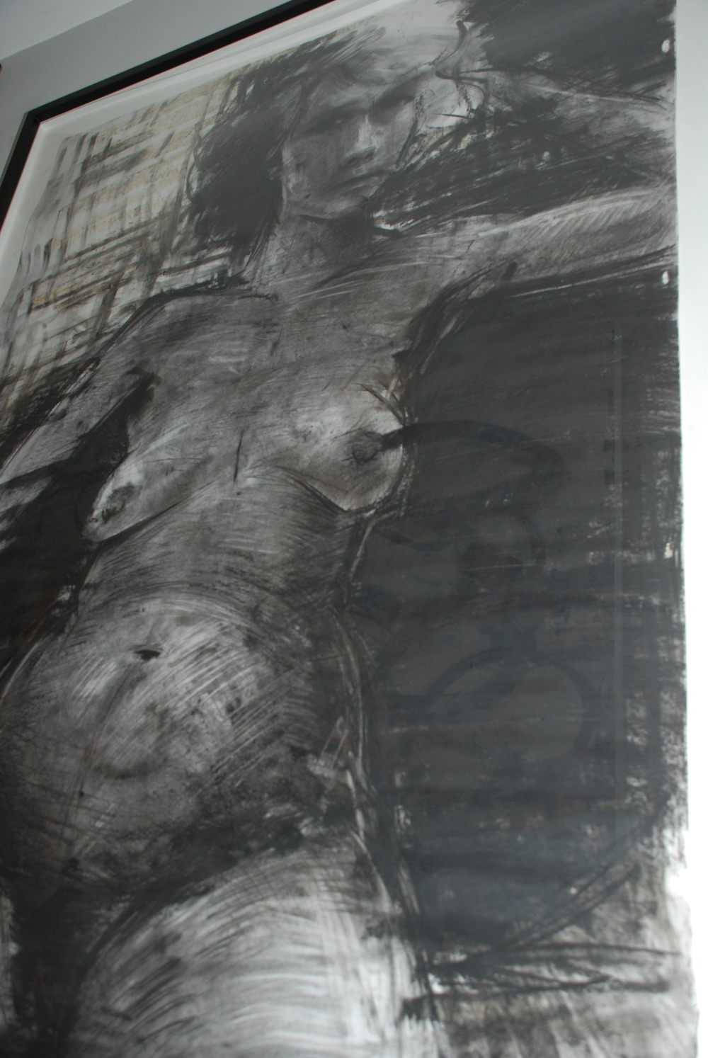 Charcoal nude hangs in the hallway.