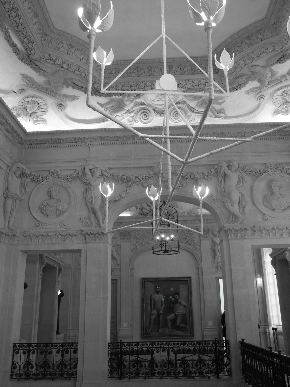 The modern white sculptural chandelier pops against the period details of the mansion, and a Picasso piece in the background.