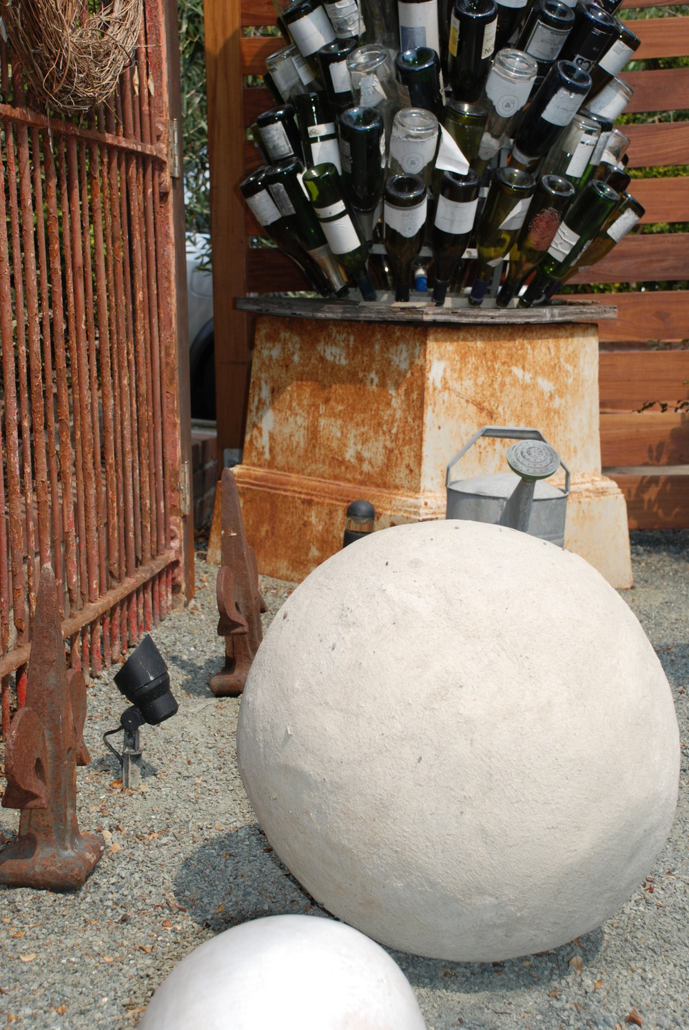 French wine bottle dryer becomes garden art alongside concrete spheres