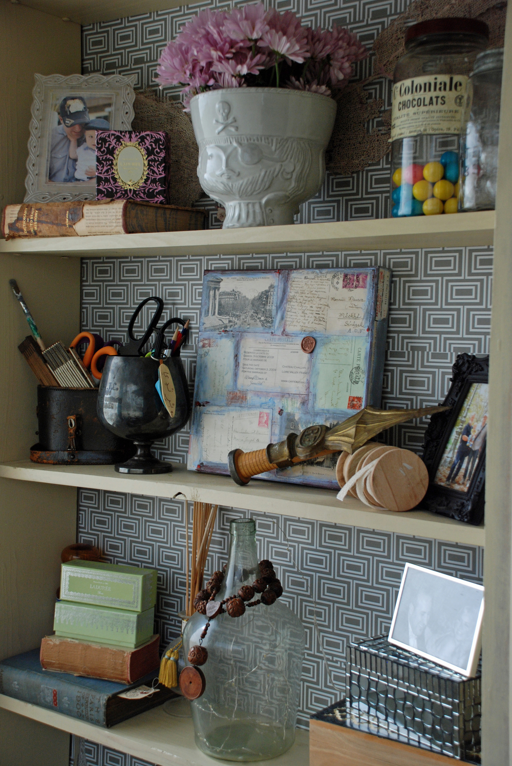 Bookshelf layered with travel mementos turned storage