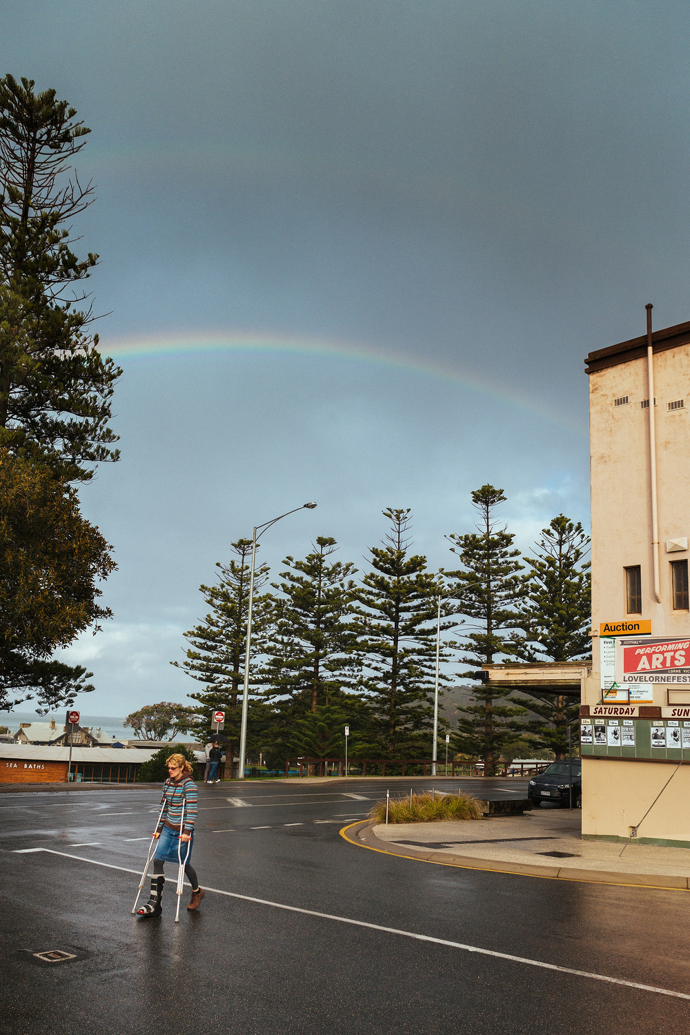 A lady on crutches crosses the road as a double rainbow forms in the sky behind her.