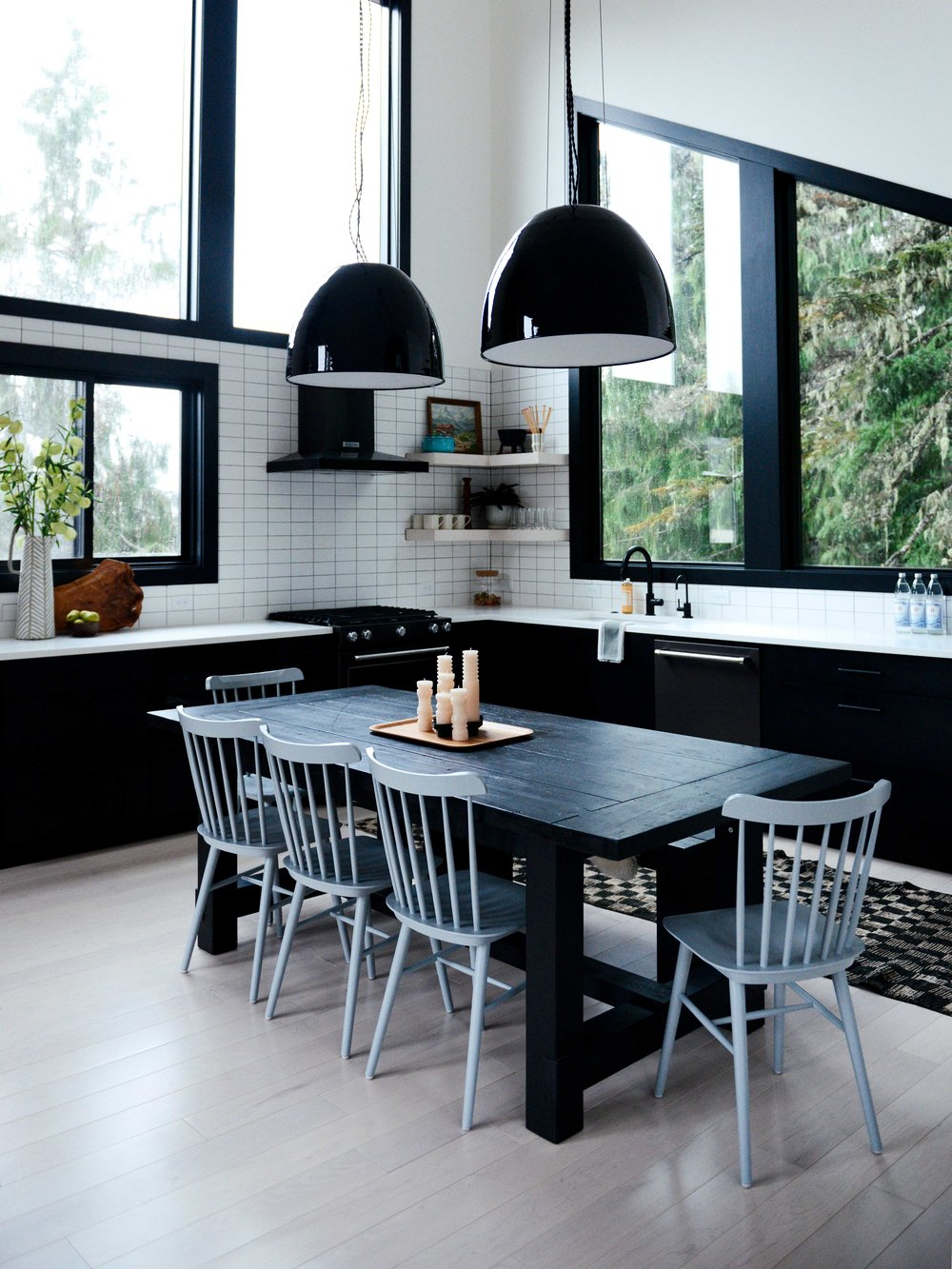 Above: A chunky black farm style table and bench are paired with light gray Windsor style chairs.  This multipurpose table is for meal prep, eating and all the fondue you can handle.